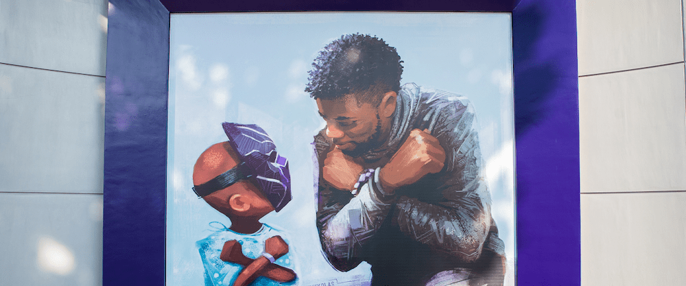 An image of a mural showing Chadwick Boseman kneeling and doing the Wakanda Forever salute to a young child wearing a Black Panther mask